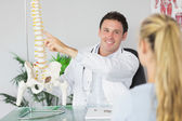 Smiling doctor showing a patient something on skeleton model — Stock Photo