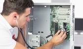 Handsome computer engineer examining hardware with stethoscope — Stock Photo