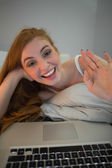 Happy redhead waving to laptop on video chat — Stock Photo