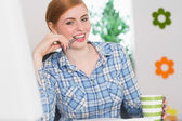 Happy redhead biting pen at her desk — Stok fotoğraf