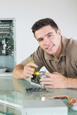 Handsome cheerful computer engineer repairing hardware with pliers — Foto de Stock