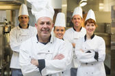 Five chefs wearing uniforms posing in a kitchen — Stock Photo