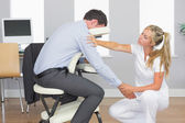 Masseuse treating clients arm in massage chair — Stock Photo