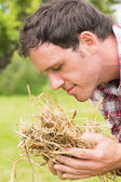 Young man smelling yellow straw — Stock Photo