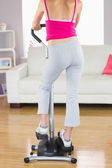 Rear view of sporty woman training on step machine — ストック写真