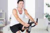 Alegre homem desportivo exercitando na bicicleta — Fotografia Stock
