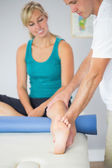 Physiotherapist examining patients leg — Stock Photo
