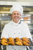 Mature baker presenting some croissants — Stock Photo