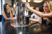 Blonde woman pulling a pint of stout — Stock Photo