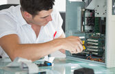 Handsome computer engineer repairing computer with pliers — Stock Photo