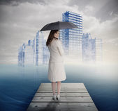 Rear view of businesswoman holding umbrella in front of holographic city — Stock Photo