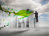 Rear view of businessman touching holographic city with green splash — Stock Photo