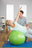 Smiling physiotherapist correcting patient doing exercise on exercise ball — Stock Photo