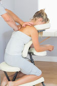 Masseur treating clients shoulder in massage chair — Stock Photo