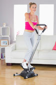 Sporty smiling blonde training on step machine — Stock Photo