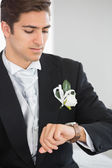 Handsome bridegroom watching the clock — Stock Photo