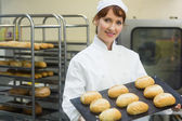 Happy female baker showing some rolls on a baking tray — Stock Photo
