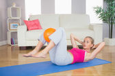 Sporty focused blonde doing sit ups holding ball between knees — Stock Photo