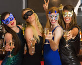 Happy friends wearing masks showing champagne glasses — Stock Photo