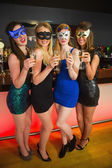 Happy friend with masks on holding champagne — Stock Photo