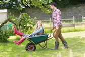 Handsome man pushing his laughing girlfriend in a wheelbarrow — Stock Photo