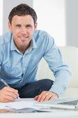 Szczęśliwy człowiek dorywczo, pisanie na arkuszach płacenia rachunków — Zdjęcie stockowe