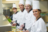 Four chefs working at serving trays — Foto Stock