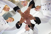 Chefs joining hands in a circle — Stock Photo