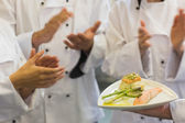 Chefs applauding a salmon dish — Stockfoto