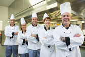 Team of chefs smiling at the camera — Stockfoto