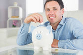 Handsome casual man putting coin in piggy bank smiling at camera — Stock Photo