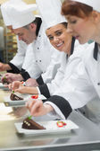 Team of chefs in a row garnishing dessert plates one girl smiling at camera — Stock Photo