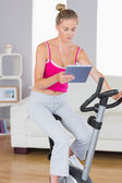 Sporty serious blonde training on exercise bike using tablet — Stock Photo