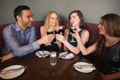 Laughing friends sitting together clinking glasses — Stock Photo