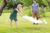 Blonde woman spreading a blanket for a picnic with her boyfriend — Stock Photo