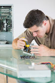 Handsome focused computer engineer repairing hardware with pliers — Stock Photo