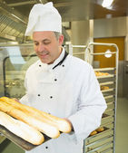 Mature head chef holding some baguettes — Stock Photo