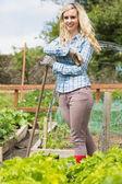 Happy blonde woman standing in her garden — Stock Photo