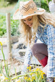 Smiling blonde woman working in the garden — Stock Photo