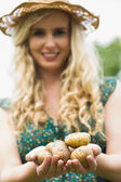 Young woman holding some potatoes — Stock Photo