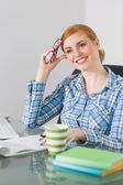 Thoughtful redhead sitting at her desk looking away holding reading glasses — Stock Photo