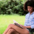 Beautiful woman reading in the park leaning against a tree — Stock Video