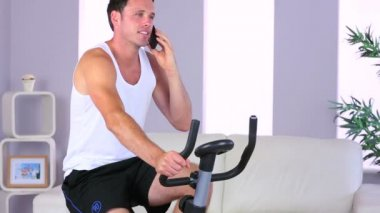 Attractive sporty man exercising on bike and phoning — Stock Video