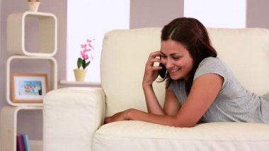 Attractive laughing brunette lying on couch phoning — Stock Video