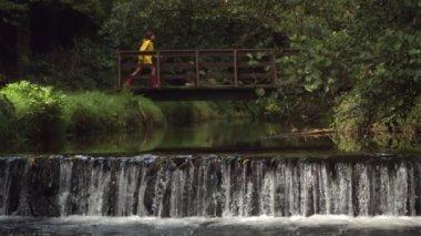 Video of idyllic waterfall with brunette running over bridge — Vídeo de stock