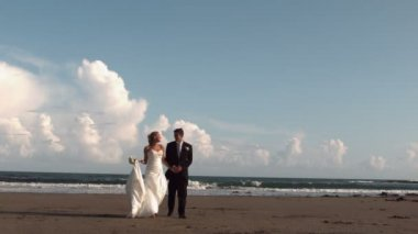 Happy newlywed couple walking on the beach — Стоковое видео