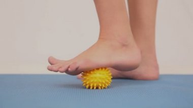 Girl using yellow massage ball on her foot — Stock Video