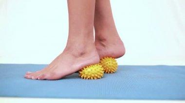 Girl using yellow massage balls on her feet — Stock Video
