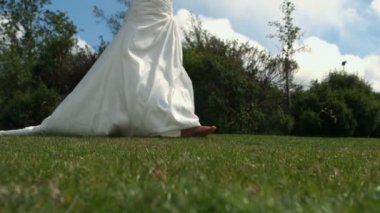 Bride in wedding dress walking on grass — Stock Video