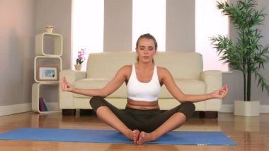Sporty brunette meditating at home — Stock Video